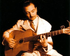 Django Reinhardt avec une guitare (petite bouche)